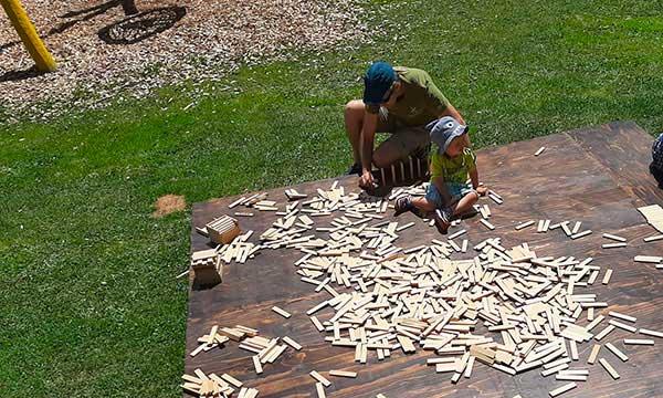 papà gioca con bimbo co ncostruzioni di legno