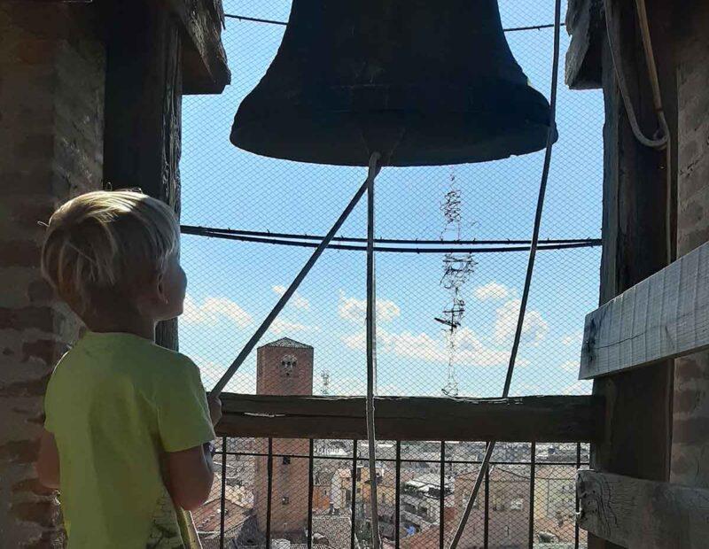 bambino suona la campana sul campanile di Alba